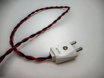 electric plug close up shot with red wire in a white background stock photography