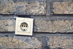 Electric plug connector, ac outlet, on brick wall. Royalty Free Stock Photo