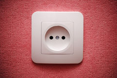 Electric plug connector (outlet) on the wall. Electric plug connector (outlet) on red wall Royalty Free Stock Image
