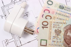 Electric plug and money on electrical drawing, energy concept Royalty Free Stock Photo