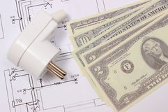 Electric plug and money on electrical drawing, energy concept Royalty Free Stock Photography