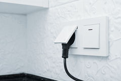 Electric plug in a socket. Closeup. Small shallow DOF Stock Image