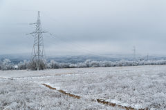 Electric pole on the background of a winter landscape. Electric pole, high-voltage line on a background of a winter landscape Stock Image