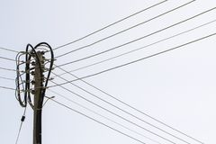 Electric pole and cables. Old wooden electric pole and cables on white sky background stock photography