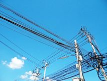 Electric pole connect to the high voltage electric wires on blue sky background Stock Photos