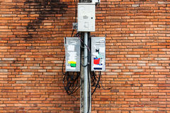 Electric pole with dirty electrical control box and cable, brick. Shoot photo with DSLR camera in light nature real time Royalty Free Stock Photo
