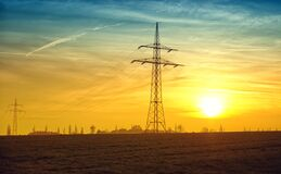 Electric pole in field at sunset Royalty Free Stock Photo