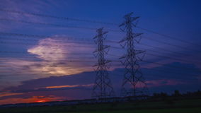 Electric pole, High voltage towers and sky sunset 4K, day to night, Timelapse Royalty Free Stock Photos