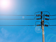 Electric pole power lines and wires with blue sky with lamp. Royalty Free Stock Photos