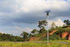 Electric pole with solar panel on road in countryside, use of So Royalty Free Stock Image