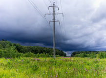 Electric pole stands in a green field. Over the field of storm c Stock Photo