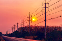 Electric pole on sunset along the road Stock Images