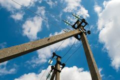 Electric pole with wires against a blue sky with clouds Royalty Free Stock Photo