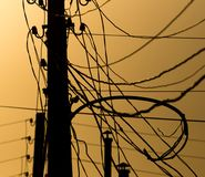 Electric pole with wires on the golden sunset.  Stock Image
