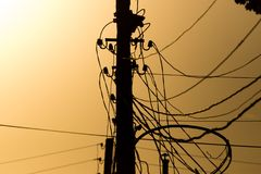 Electric pole with wires on the golden sunset.  Royalty Free Stock Image