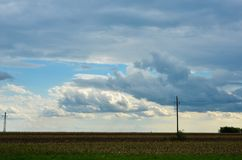 Electric poles in distant with dramatic clouds and sky Royalty Free Stock Images