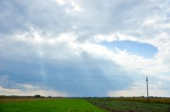 Electric poles in distant with dramatic clouds and sky Royalty Free Stock Image