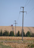 Electric poles and network in field. With combine in background Stock Photos