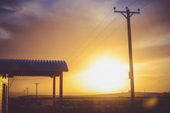 Electric Post and Waiting Shed During Sunset Stock Images