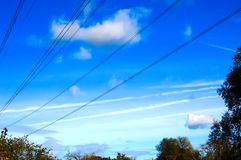 Electric power cables and thin clouds streak the sky stock photo