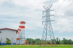 Electric power generator and pylon. Natural gas powered electric generator station and pylon in secured open green surrounding area Stock Photo
