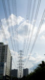 Electric power line with high voltage tower at far sight and bui Royalty Free Stock Image