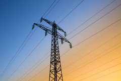 Electric power lines. Against blue and yellow sky stock image