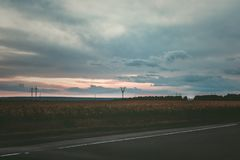 Electric power lines at sunset, and asphalt road. In the foreground. Toned, style photo Stock Photo