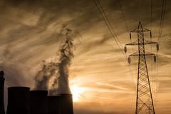 Electric power plant at dusk with orange sky in Kozani Greece Royalty Free Stock Photography