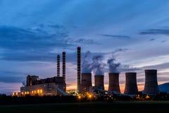 Electric power plant at dusk with orange sky in Kozani Greece Royalty Free Stock Photo