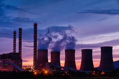 Electric power plant at dusk with orange sky in Kozani Greece Royalty Free Stock Photos