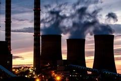 Electric power plant at dusk with orange sky in Kozani Greece Stock Image