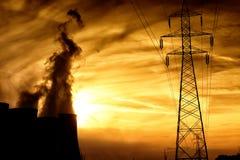 Electric power plant at dusk with orange sky in Kozani Greece.  Stock Photo