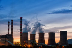 Electric power plant at dusk with orange sky in Kozani Greece.  Royalty Free Stock Photos