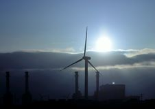 Electric power plant and wind turbine backlit at dawn Stock Image