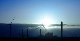 Electric power plant and wind turbines at sunrise Stock Photography