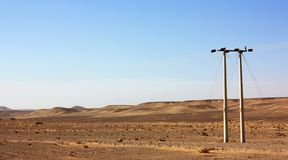 Electric power poles in desert of Jordan, high voltage powerlines, early morning in wilderness. Electric power poles in desert of Jordan. High voltage royalty free stock image