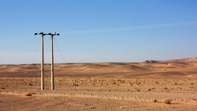 Electric power poles in desert of Jordan, high voltage powerlines, early morning in wilderness. Electric power poles in desert of Jordan. High voltage royalty free stock images