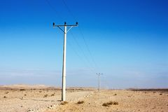 Electric power poles in desert of Jordan, high voltage powerlines, early morning in wilderness. Electric power poles in desert of Jordan. High voltage stock photography