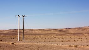 Electric power poles in desert of Jordan, high voltage powerlines, early morning in wilderness. Electric power poles in desert of Jordan. High voltage royalty free stock photos