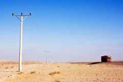 Electric power poles in desert of Jordan, high voltage powerlines, red truck on morning road. Electric power poles in desert of Jordan. High voltage powerlines stock photography