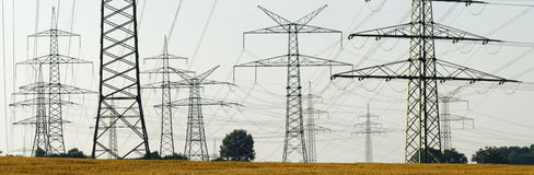 Electric power poles. Panorama view to big group of electric power poles royalty free stock photo