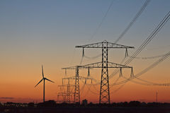 Electric power posts and wind turbine Royalty Free Stock Photo