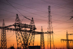 Electric power pylons. High voltage power pylons (electric poles) conducting electrical energy Stock Photography