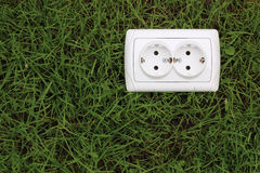Electric power receptacle on grass background Royalty Free Stock Photos