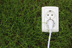 Electric power receptacle on grass background Royalty Free Stock Photography