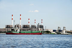 Electric power refinery plant and logistic ship. Electric power refinery plant in Thailand foreground with red green ship in the Chao praya river royalty free stock photo