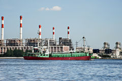 Electric power refinery plant. In Thailand foreground with red green ship in the Chao praya river royalty free stock images