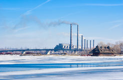 Electric power station beside a frozen river Royalty Free Stock Photos