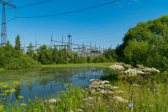 Power station near the pond. Power lines. Royalty Free Stock Images